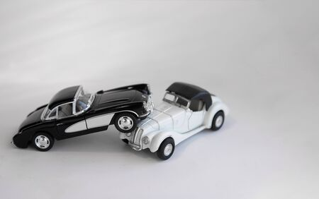 Collision of two retro cars toys on a white background