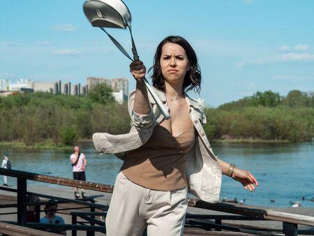 Young woman waving her handbag, defending herself, face tense
