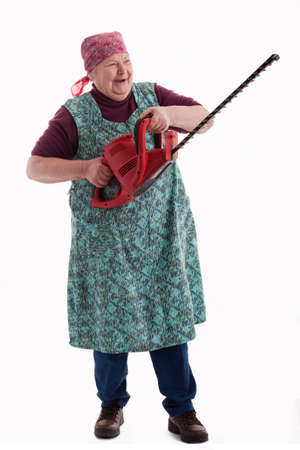 electric trimmer: A lusty female senior with garden saw  looks to viewer 2