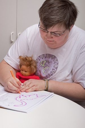 mentally: a sitting mentally disabled woman is painting a picture