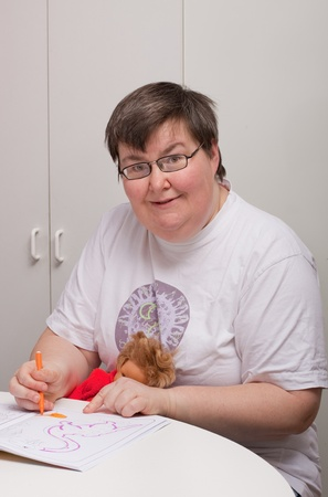 a sitting mentally disabled woman is painting a picture photo