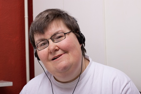 mentally: a sitting mentally disabled woman is listening to music
