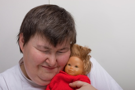 a sitting mentally disabled woman cuddles a doll Stock Photo - 12901031