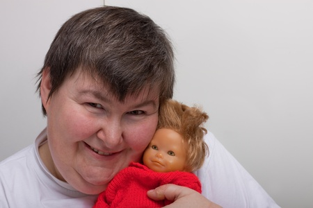 mentally: a sitting mentally disabled woman cuddles a doll Stock Photo