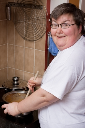 mentally: a mentally disabled woman is cooking in the kitchen Stock Photo