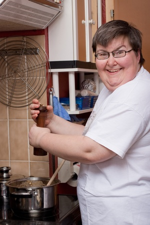 people with disabilities: a mentally disabled woman is cooking in the kitchen Stock Photo