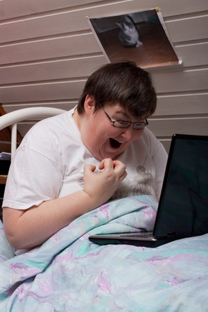 mentally disabled woman in her bed with laptop looks excited photo