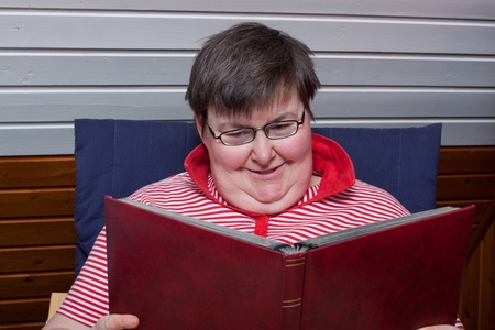 a sitting mentaly disabled woman reads and smiles Stock Photo - 12901452