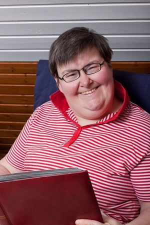 a sitting mentaly disabled woman reads and smiles photo