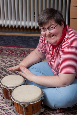 musicoterapia: una donna seduta mentaly disattivato fare musica e guarda eccitato Archivio Fotografico