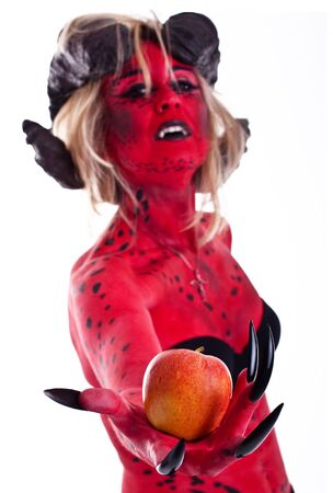 devil woman: a devil woman with an apple Stock Photo