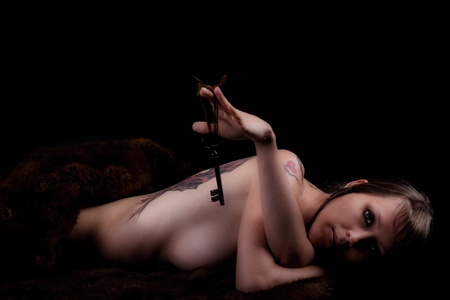 a pretty nude girl with a key in her hand Stock Photo - 13150191