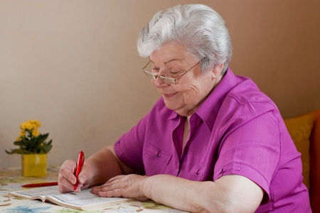 pensioner puzzles and smiles with reading glasses