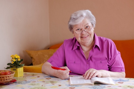 elderly woman with reading glasses sitting on the couch and smiles