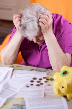 chequera: Anciana se sienta delante de los papeles y desesperados Foto de archivo