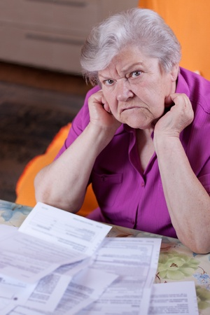 pensioner: Pensioner with papers before her, looking desperately to the viewer