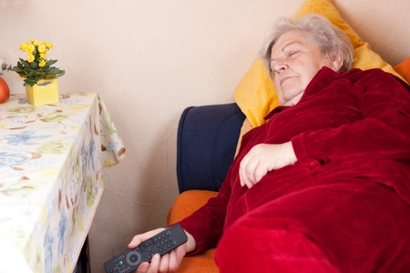 Elderly woman lying on the couch with remote in hand and sleeps photo