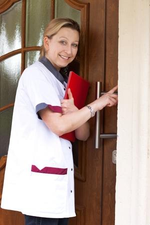 Enfermera geriátrica hace una llamada de casa y los anillos de la puerta