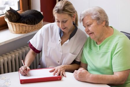 blond nurse visiting a senior patient at home Stock Photo