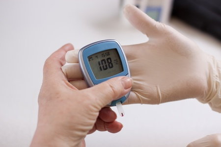 Geriatric nurse measures with glucose meter Stock Photo - 13463149