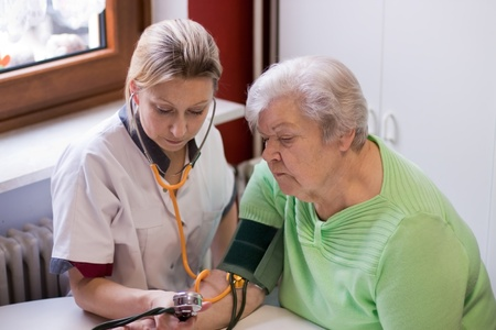 measured: nurse makes home visits and measured blood pressure Stock Photo