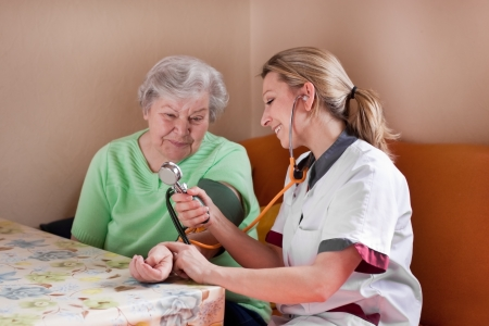 nursing homes: nurse measures the blood pressure of a patient