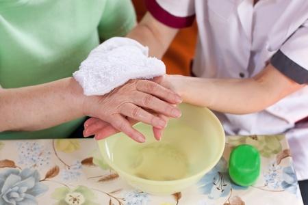 aide a domicile: jeune infirmi�re se lave les mains d'une femme �g�e