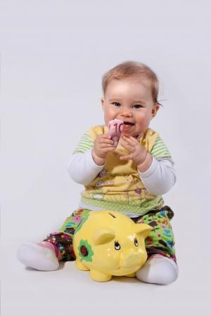 Femmina adorabile bambino sorride con banconota tra le mani Archivio Fotografico - 13612394