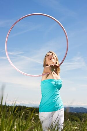happy pretty woman standing on a lawn and plays with hula hoops  In the background mountains photo