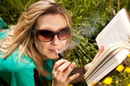 mooie blonde vrouwenlezing en ingedampt een elektrische sigaret