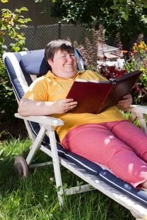 mentally disabled woman reading a book in the garden photo