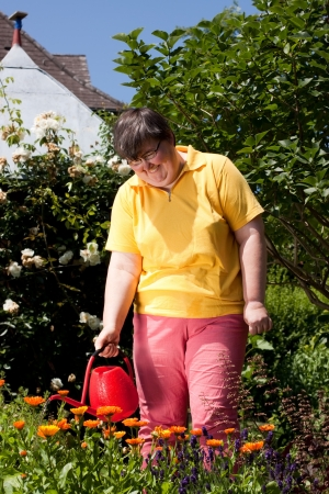 mentally disabled woman stands in the garden and  poured  flowers Stock Photo - 14164601