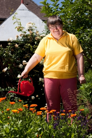mentally disabled woman stands in the garden and  pours flowers