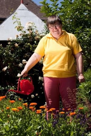 personas discapacitadas: mujer mentalmente discapacitada se encuentra en el jardín y derrama flores