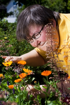 mentally: mentally disabled woman cut flowers in the garden