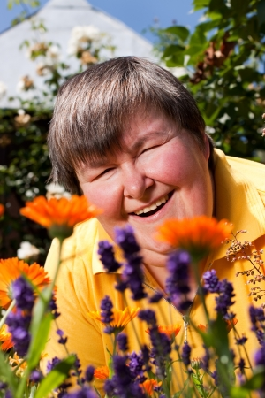 mentally disabled woman is in the garden and smell of flowers photo