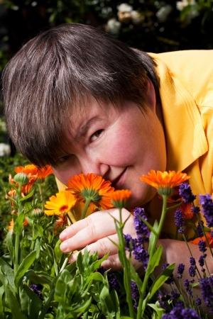 mentally disabled woman is in the garden and smell on flowers Stock Photo
