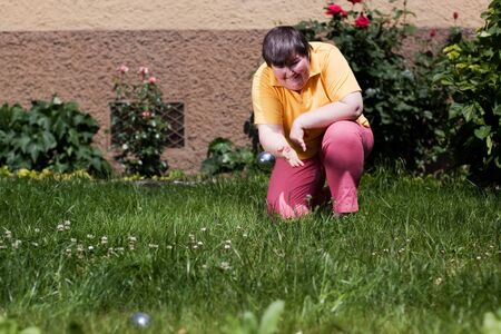 mentally disabled woman kneeling in the garden and  throws bowls ball photo