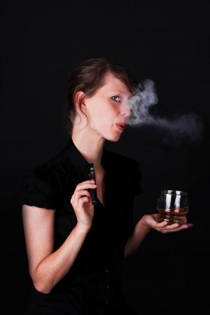 jolie jeune femme avec la cigarette �lectrique et le whisky photo