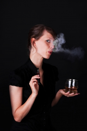 pretty young woman with electric cigarette and whiskey photo