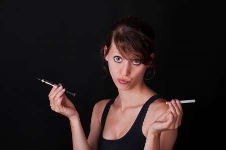 ordinary woman: young woman have to decide between electric cigarette and an ordinary Stock Photo