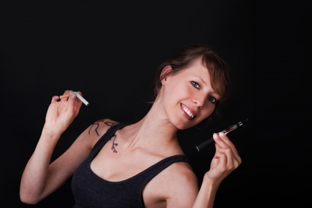 pretty young woman have to decide between electric cigarette and an ordinary photo