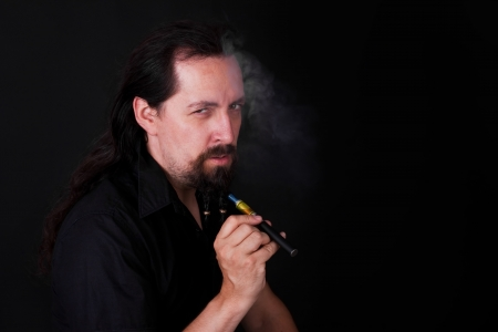 long haired man with electric cigarette photo