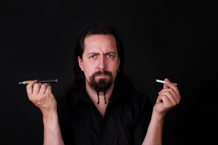 attractive man have to decide between an electric cigarette and an ordinary photo
