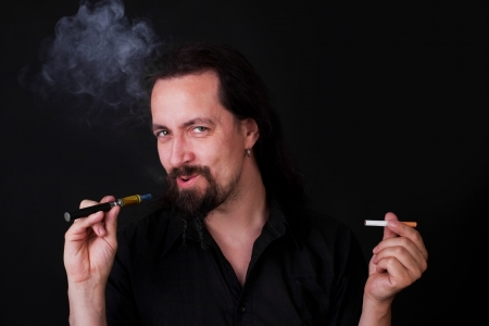 decide: attractive man have to decide between an e-cigarette and an ordinary Stock Photo