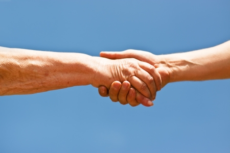 two hands shaking hands over blue sky Stock Photo