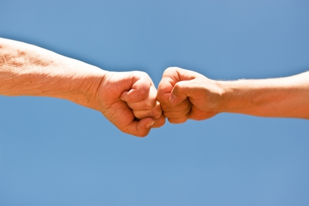 two fists punching each other over blue sky photo