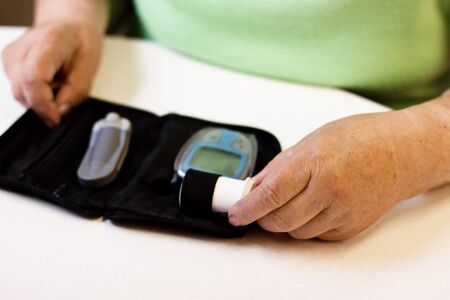 diabetes needles: hands of senior with equipment of blood sugar test