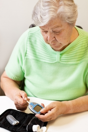 blood glucose: old woman with test strip and blood glucose meter