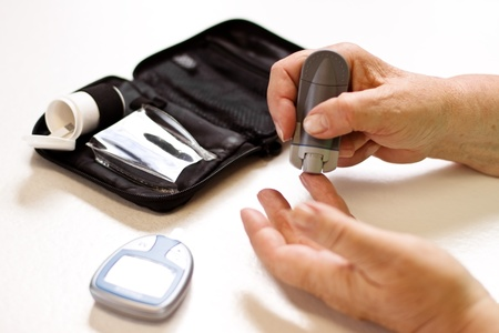 senior with equipment of blood sugar test